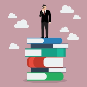 Businessman standing on stack of books with a magnifying glass. Business vision